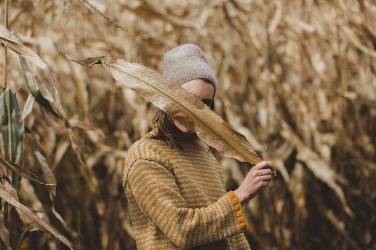 woman-hides-behind-dry-harvest-leaves_4460x4460
